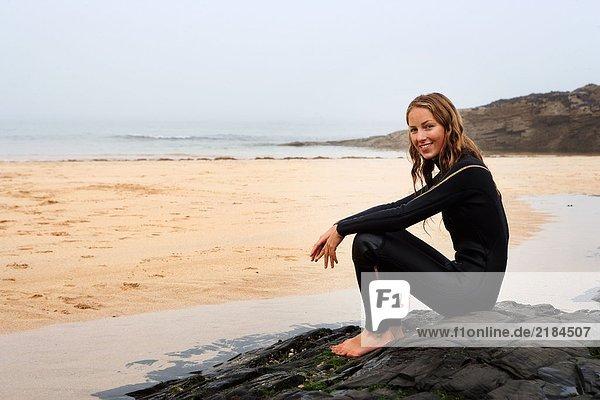 Frau im Neoprenanzug lächelnd am Strand sitzend.
