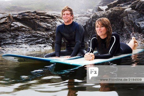 Paar auf Surfbrettern im Wasser liegend  lächelnd.