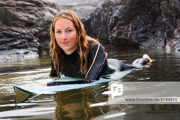 Frau lächelnd auf dem Surfbrett im Wasser liegend.