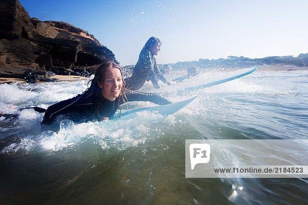 Vier Leute im Wasser mit lächelnden Surfbrettern.