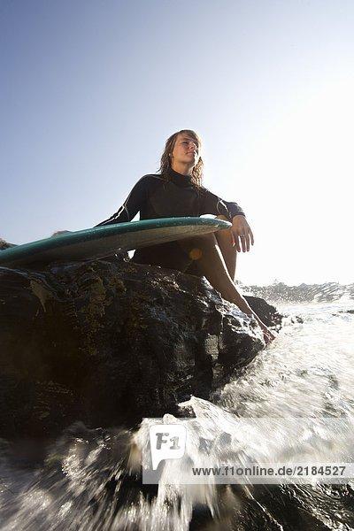 Frau sitzt auf großen Felsen mit Surfbrett.