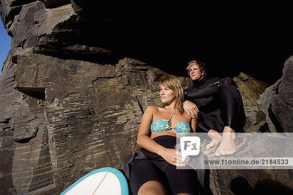 Ein Paar sitzt auf großen Felsen mit einem Surfbrett.