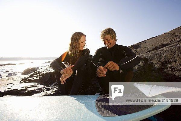 Paar am Strand sitzend mit lächelndem Surfbrett.