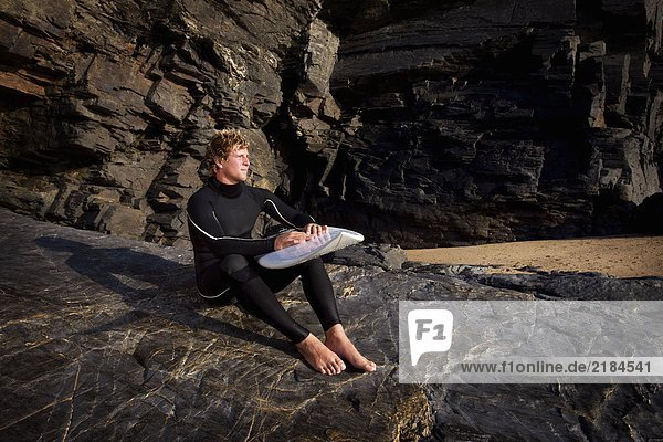 Mann sitzt auf großem Felsen im Neoprenanzug mit Surfbrett auf dem Schoß.