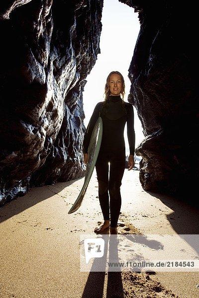 Frau steht mit Surfbrett zwischen großen Felsen und lächelt.