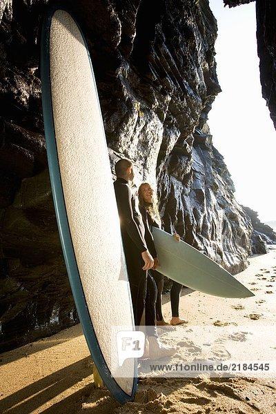 Paar stehend mit Surfbrettern bei großen Felsen lächelnd.