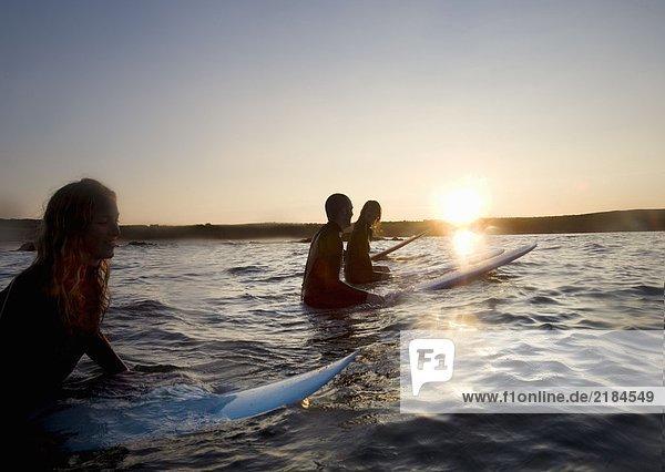 Vier Leute sitzen auf Surfbrettern im Wasser und lächeln.