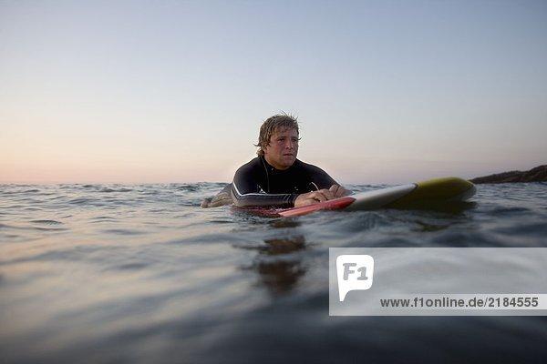 Mann auf dem Surfbrett im Wasser liegend.