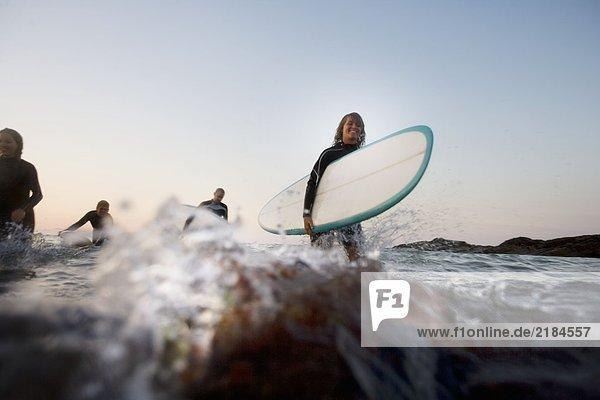 Vier Leute mit Surfbrettern im Wasser.