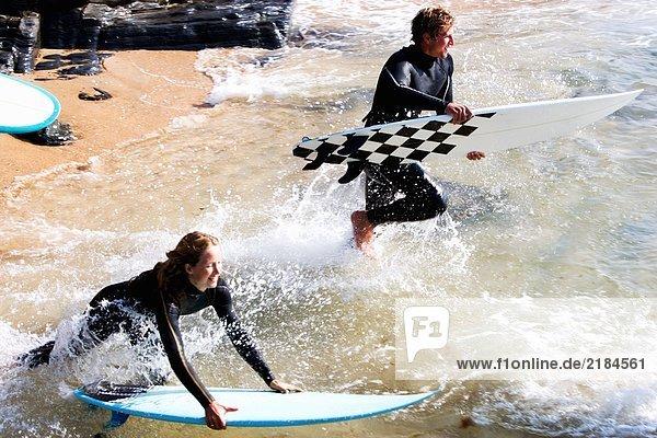 Paar mit Surfbrettern  die lächelnd im Wasser planschen.