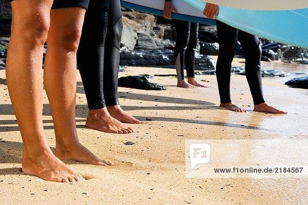 Vier Beine an einem Strand mit zwei Leuten  die Surfbretter halten.