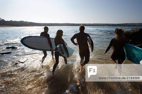 Vier Leute laufen mit Surfbrettern ins Wasser.