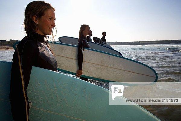 Vier Leute stehen mit Surfbrettern im Wasser und lächeln.