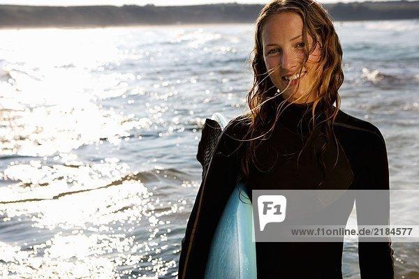 Frau stehend mit einem Surfbrett lächelnd.