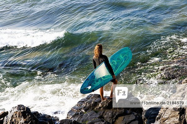 Frau steht mit einem Surfbrett auf großen Felsen.
