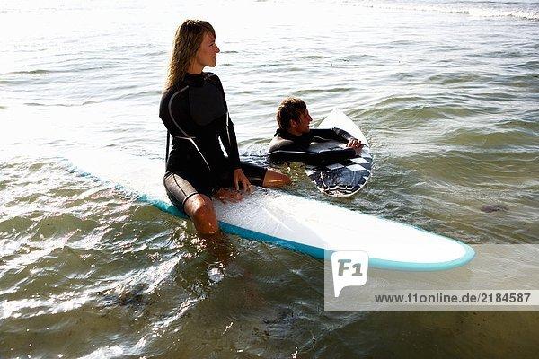Ein Paar schwebt auf Surfbrettern im Wasser und lächelt.