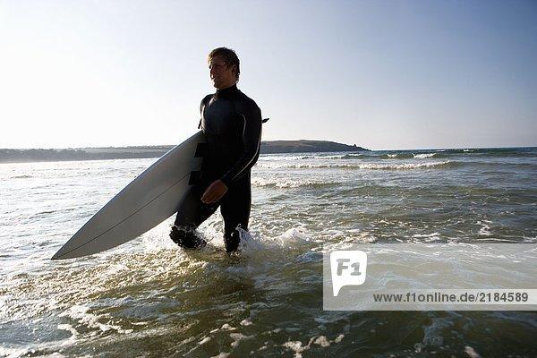 Mann geht mit einem Surfbrett im Wasser und lächelt.