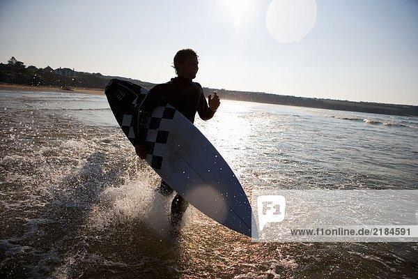 Mann läuft mit lächelndem Surfbrett durchs Wasser.