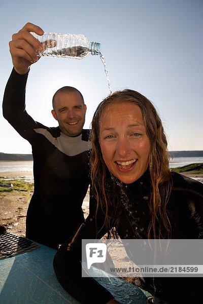 Mann gießt Wasser über den Kopf der lachenden Frau mit dem Surfbrett auf dem Schoß.
