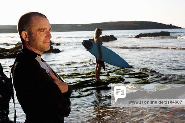 Mann steht lächelnd mit einer Frau  die das Surfbrett im Hintergrund hält.