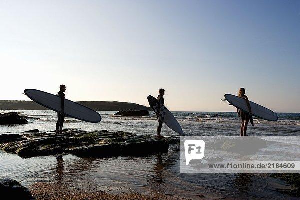 Drei Leute halten Surfbretter auf großen Felsen.