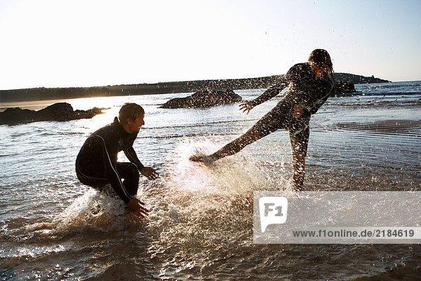 Paar in Neoprenanzügen  die im flachen Wasser spritzen.