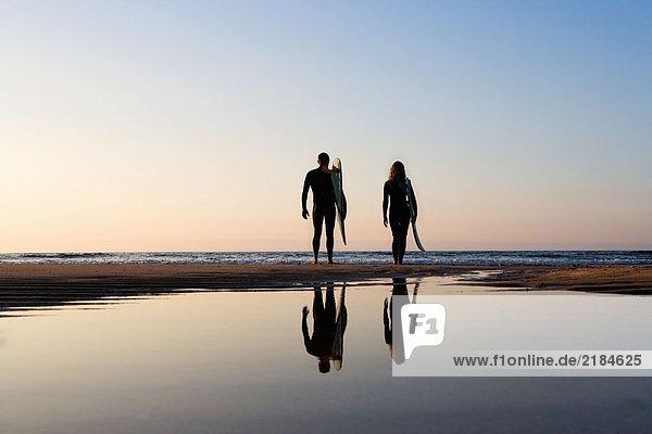 Paar am Strand stehend mit Surfbrettern.