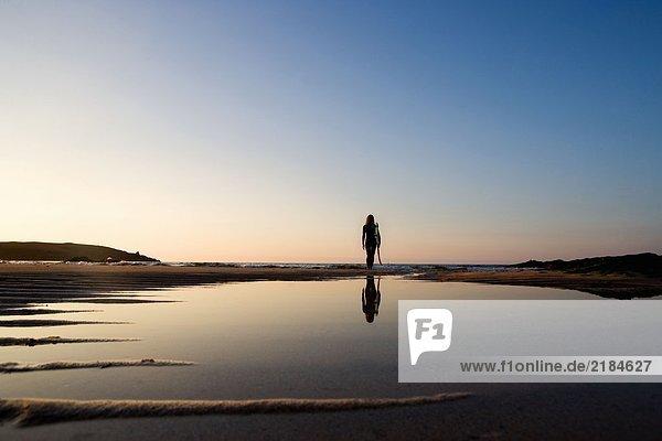 Frau steht am Strand und hält Surfbrett.