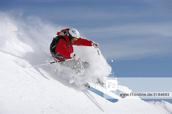 Österreich  Saalbach  Mann auf der Piste mit Schneespray