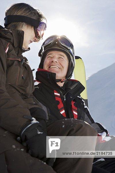 Älteres Paar in Skibekleidung mit Skiern am Berg  Nahaufnahme  Tiefblick