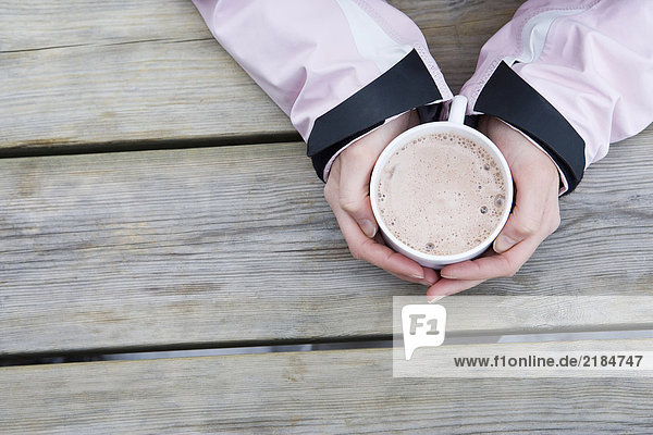 Junge Frauenhände halten Tasse heiße Schokolade  Nahaufnahme  Hochwinkelaufnahme
