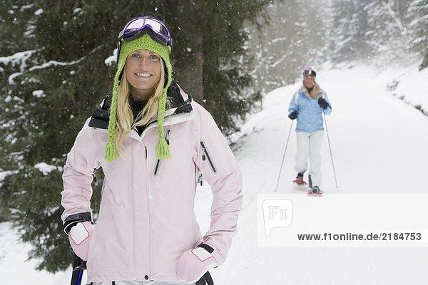 Junge Frau lächelt auf der Piste  Person im Hintergrund auf Schneeschuhen  Portrait