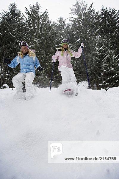Tiefblick auf zwei junge blonde Frauen  die mit Schneeschuhen den kleinen Hügel im Wald hinuntergehen.