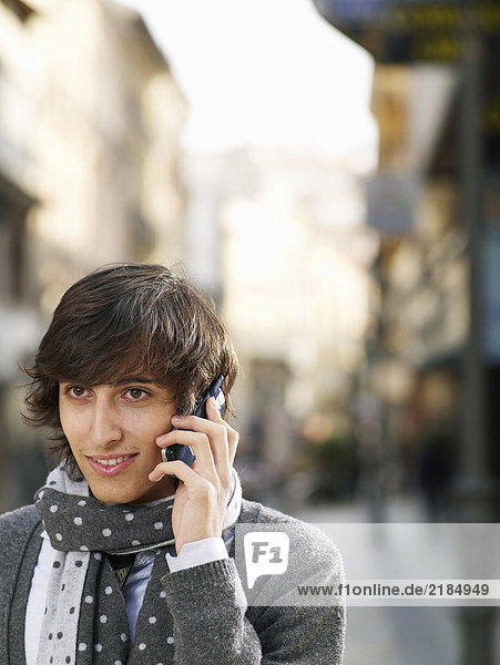 Young man standing in street using mobile phone  smiling  close-up