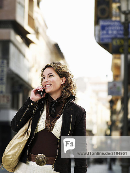 Young woman standing in street using mobile phone  smiling