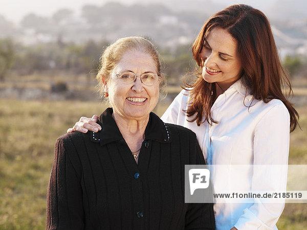 Seniorin stehend mit Tochter im Feld  lächelnd  Portrait