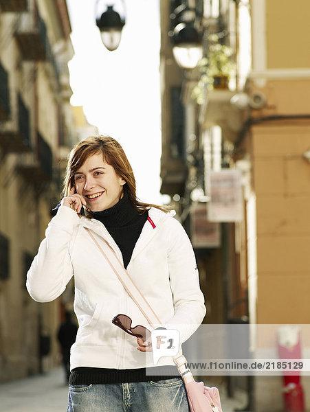 Junge Frau mit Handy auf der Straße  lächelnd