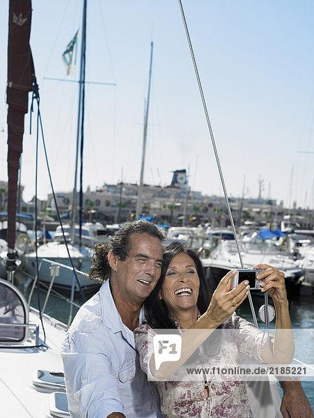 Reife Paare  die sich auf der Yacht fotografieren  lächelnd