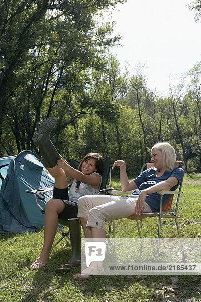 Zwei Frauen sitzen auf dem Campingplatz und lachen  eine zieht sich Stiefel an.