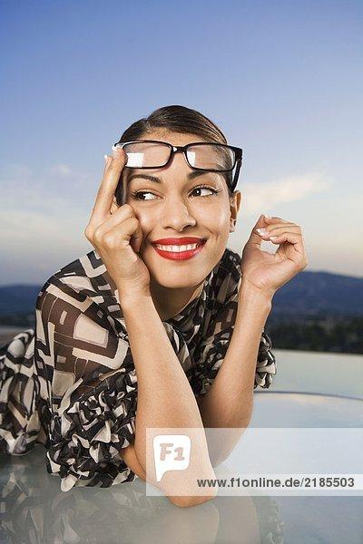 Frau schiebt eine Brille auf den Kopf und lächelt im Freien.