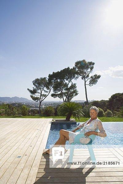 Ältere Frau entspannt sich am Pool.