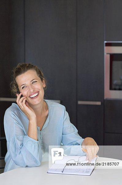 Eine Frau in der Küche  die telefoniert.