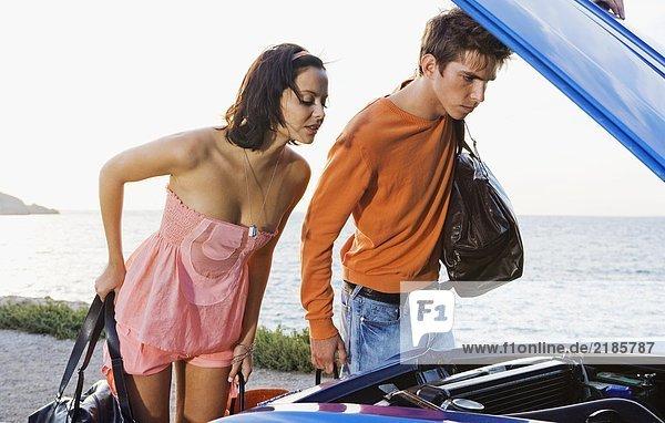 Mann und Frau schauen unter die Motorhaube.