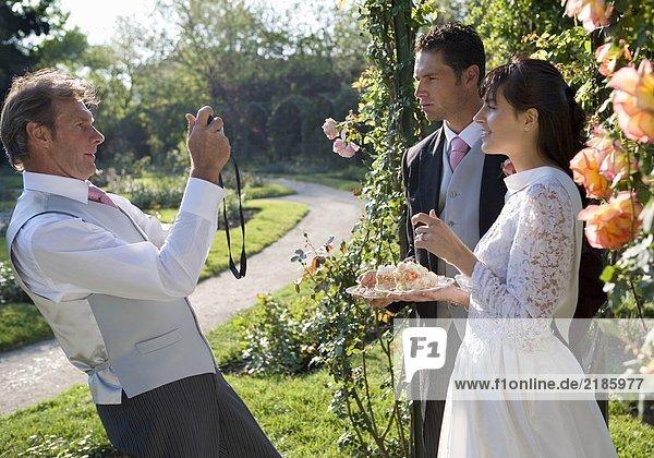 Der reife Vater fotografiert Braut und Bräutigam im Garten.