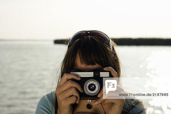 Mädchen fotografiert mit alter Kamera.