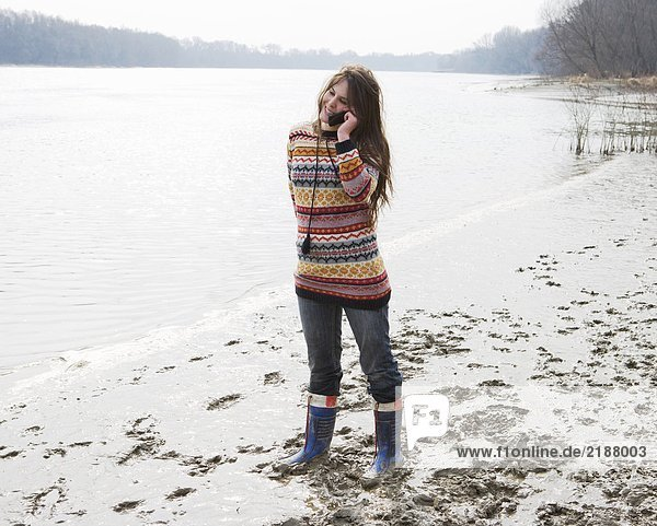 Young woman standing by river  using mobile phone  smiling