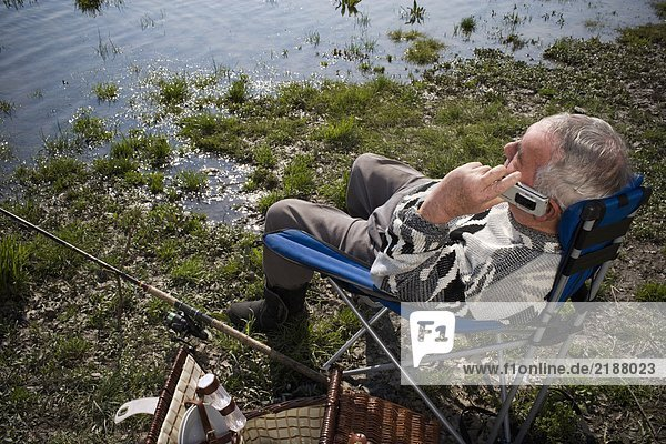 Senior man fishing by river  using mobile phone  overhead view