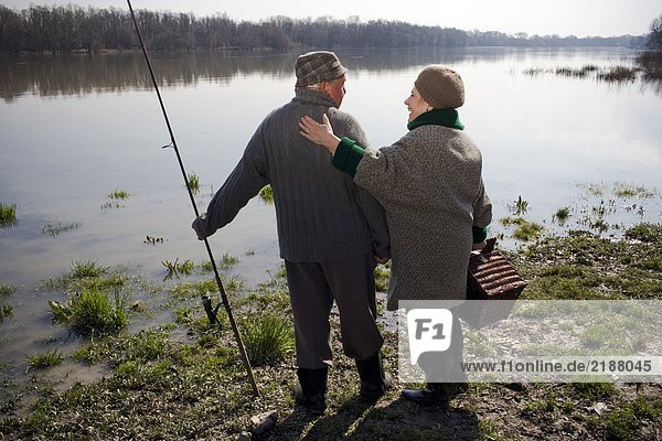 Senior couple standing by river  holding fishing rod and basket