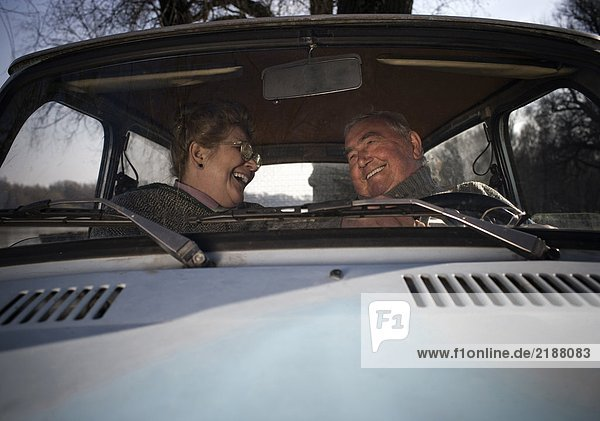 Senior couple sitting in car  smiling at each other