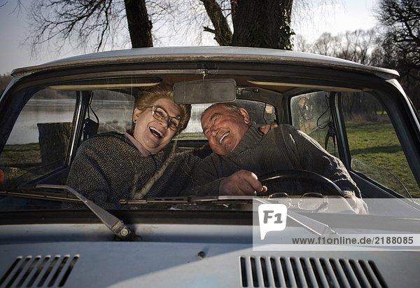 Seniorenpaar im Auto sitzend  lachend  Blick durchs Fenster